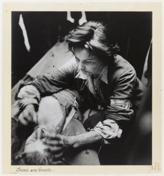 La Libération de Paris. Une jeune femme prénommée Anita dispense des Soins à un blessé Allemand, le 21 août 1944. Soins aux blessés.