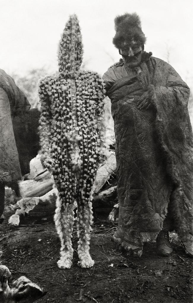 K'terrnen, le bébé de l'ogresse Xalpen, est présenté aux femmes par le chaman Tenenesk. Entièrement peint d'ocre rouge, son corps est couvert de duvet d'outarde. Cérémonie du Hain, rite Selk'nam, 1923 © Martin Gusinde / Anthropos Institut / Éditions Xavier Barral